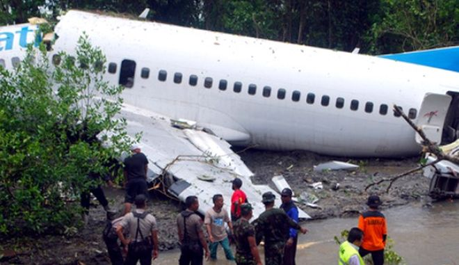 epa02114785 Rescuers inspect the site where a commercial plane skidded off the runway at Manokwari airport in West Papua, Indonesia 13 April 2010. An Indonesian plane with over 100 people on board skidded off the runway at an airport in West Papua province on 13 April injuring at least 20 people, officials and media reports said. The injured people were taken to a nearby hospital. Local media reported that the incident took place during heavy rain.  EPA/SRIWIJAYA PAJA