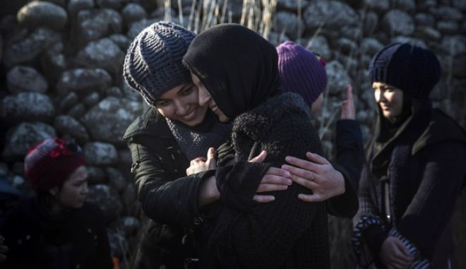 Two women hug each other after their arrival , from Turkey to the  shores of the Greek island of Lesbos, on an dinghy overcrowded by refugees and migrants, Friday, Dec. 25, 2015. The International Organization for Migrants said more than 1 million people have entered Europe earlier this week. Almost all came by sea, while 3,692 drowned in the attempt.(AP Photo/Santi Palacios)