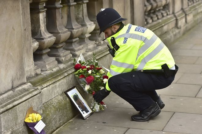 A police officer places flowers and a photo of fellow police officer Keith Palmer, who was killed in yesterdays attack, on Whitehall near the Houses of Parliament in London, Thursday March 23, 2017. On Wednesday a knife-wielding man went on a deadly rampage, first driving a car into pedestrians then stabbing a police officer to death before being fatally shot by police within Parliament's grounds in London. (Dominic Lipinski/PA via AP)