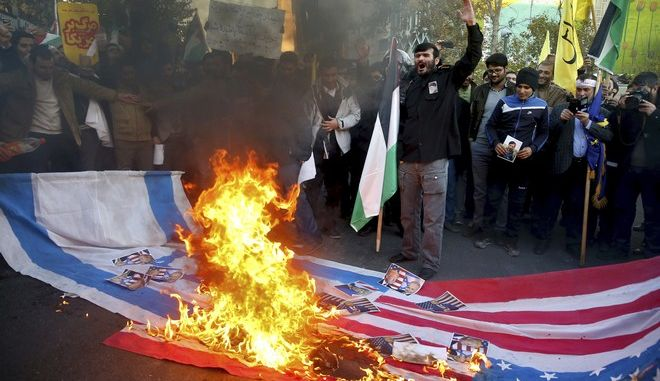 Iranian protesters burn representations of U.S. and Israeli flags during a rally against U.S. President Donald Trump's decision to recognize Jerusalem as the capital of Israel, in Tehran, Iran, Monday, Dec. 11, 2017. (AP Photo/Ebrahim Noroozi)