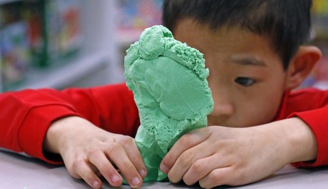 In this Tuesday, Dec. 13, 2016, photo, Paxton Mathis, 8, plays with a bright-colored molding clay at Time 4 Toys, in Flowood, Miss. The youngest child of store owner Bethany Mathis, Paxton, who has sensory processing disorder, often tests out some of the multipurpose toys offered in his mother's toy store. (AP Photo/Rogelio V. Solis)