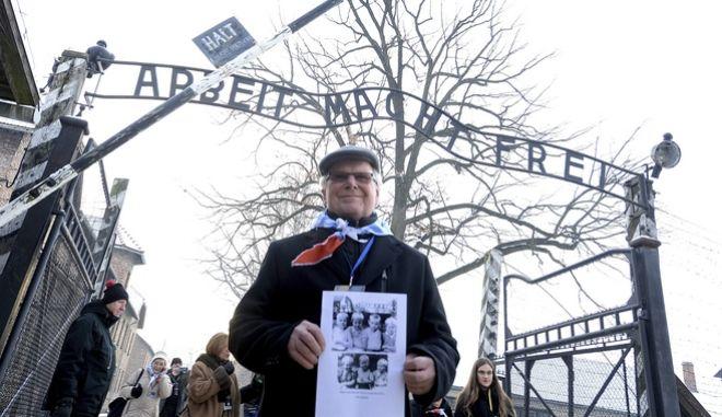Ένας επιζών κρατά μια αφίσα στο πρώην στρατόπεδο συγκέντρωσης των Ναζί, Άουσβιτς, καθώς παρευρίσκεται σε τελετή για την 74η επέτειο της απελευθέρωσης του στρατοπέδου, Κυριακή, 27 Ιανουαρίου 2019.
