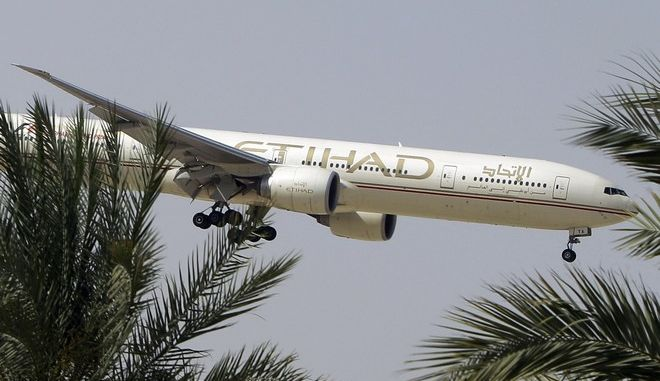 FILE- In this Sunday, May 4, 2014 file photo, an Etihad Airways plane prepares to land in Abu Dhabi Airport, United Arab Emirates. The United Arab Emirates' national airline says it is working with Australian police in its investigation into an attempted airplane attack. (AP Photo/Kamran Jebreili, File)