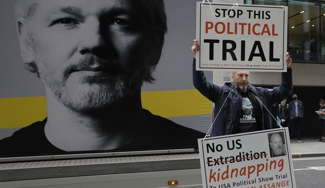 A demonstrator holds placards near the Central Criminal Court Old Bailey in London, Tuesday, Sept. 8, 2020. Lawyers for WikiLeaks founder Julian Assange and the U.S. government were squaring off in a London court on Monday at a high-stakes extradition case delayed by the coronavirus pandemic. American prosecutors have indicted the 49-year-old Australian on 18 espionage and computer misuse charges over Wikileaks' publication of secret U.S. military documents a decade ago. The charges carry a maximum sentence of 175 years in prison. (AP Photo/Kirsty Wigglesworth)