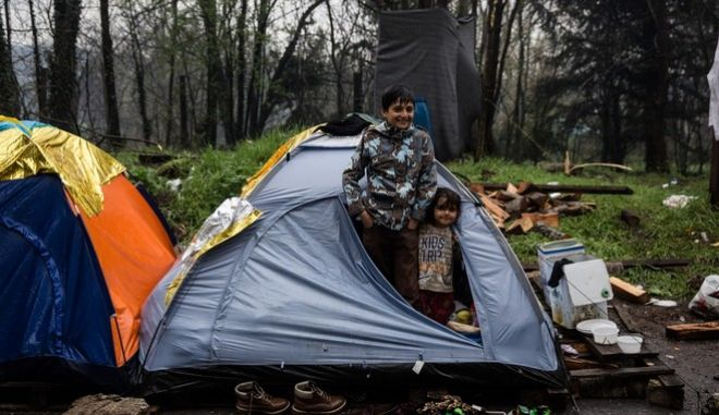 Children stands inside their tent during a rain at a makeshift refugee camp at the Greek - FYROM border near the village of Idomeni, Greece on March 13, 2016.