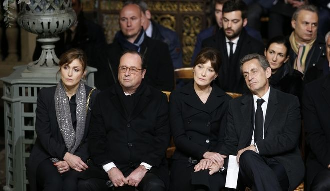 Former French presidents Nicolas Sarkozy, right, Francois Hollande, Carla Bruni Sarkozy, 2nd right, and Julie Gayet, left, attend the funeral service of French rocker Johnny Hallyday at the Madeleine church, in Paris, France, Saturday, Dec. 9, 2017. France is bidding farewell to its biggest rock star, honoring Johnny Hallyday with an exceptional funeral procession down the Champs-Elysees, a presidential speech and a motorcycle parade  all under intense security. (AP Photo/Thibault Camus, Pool)