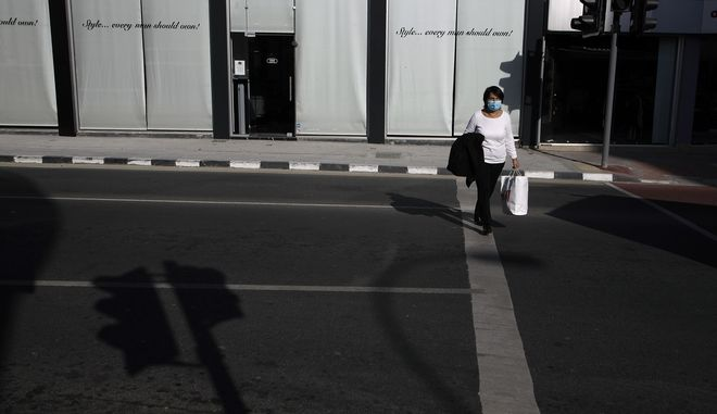 A woman wearing face mask crosses a street in central Nicosia, Friday, Jan. 8, 2021. Cyprus is returning to lockdown mode for the remainder of the month with daytime restrictions on movement and a shuttering of schools after the country's health minister conceded that a raft of tough measures already in place including a night-time curfew weren't enough to curtail the spread of the coronavirus. (AP Photo/Petros Karadjias)