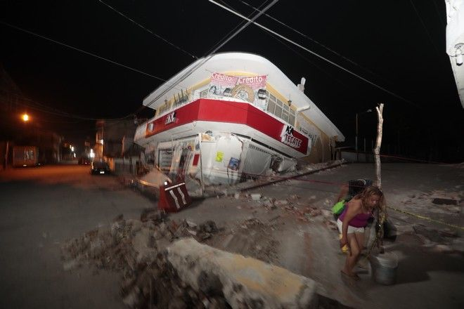 A woman walks past a collapsed building after a 7.1 earthquake, in Jojutla, Morelos state, Mexico, Tuesday, Sept. 19, 2017. The earthquake stunned central Mexico, killing more than 100 people as buildings collapsed in plumes of dust. (AP Photo/Eduardo Verdugo)
