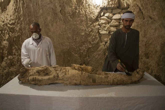 Egyptian excavation workers restore a mummy in a newly discovered tomb on Luxor's West Bank known as