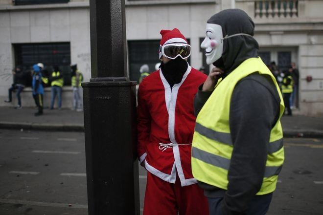 Διαδηλωτής ως Άγιος Βασίλης συζητά με διαδηλωτής με μάσκα του Guy Fawkes, εν μέσω των διαδηλώσεων των κίτρινων γιλέκων στο Παρίσι