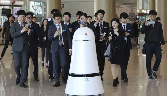 In this April 10, 2017 photo, employees of Incheon International Airport follow Troika, a self-driving robot made by LG Electronics, which moves around for visitors at the Incheon International Airport in Incheon, South Korea. Robots will start roaming South Koreas largest airport this summer, helping travelers find their boarding gates and keep its floors clean as the country prepares for its first Winter Olympics game. (AP Photo/Ahn Young-joon)