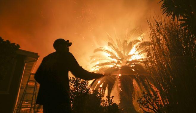 Άνδρας ρίχνει νερό στην αυλή του καθώς οι μεγάλη πυρκαγιά πλησιάζει το σπίτι στου στο Μαλιμπού της Καλιφόρνια