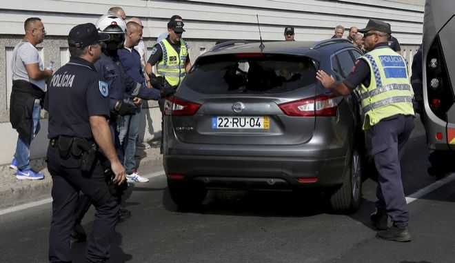 Police escort a driver after his car was damaged during a protest held by taxi drivers against Uber and Cabify in Lisbon, Monday, Oct. 10, 2016. Several thousand taxis have snarled morning rush-hour traffic in the Portuguese capital to protest against ride-hailing apps, complaining that this companies are not covered by the same tax, training and safety regulations as they are. (AP Photo/Steven Governo)