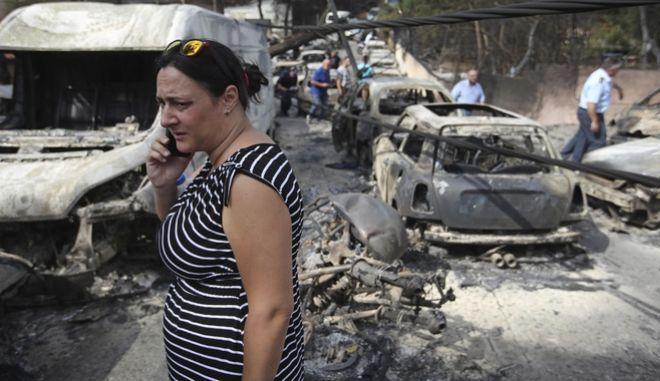 Γυναίκα με δάκρυα στα μάτια μιλά στο τηλέφωνο στο Μάτι Αττικής ανάμεσα σε καμμένα αυτοκίνητα