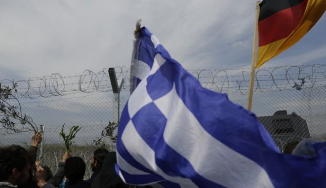 Migrant people caring Greece flag visiting fence border to greet the Macedonian police after  yesterday riots at the fence at the makeshift camp at the northern Greek border point of Idomeni, Greece, Monday, April 11, 2016. More than 12,000 people have been stuck here for more than a month amid hopes that the border would reopen.(AP Photo/Amel Emric)