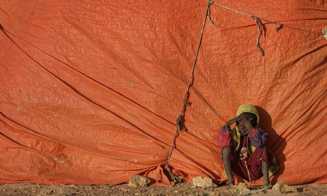A young Somali boy sits outside his makeshift hut at a camp for people displaced from their homes elsewhere in the country by the drought, shortly after dawn in Qardho, Somalia Thursday, March 9, 2017. Somalia's government has declared the drought a national disaster, and the United Nations estimates that 5 million people in this Horn of Africa nation need aid, amid warnings of a full-blown famine. (AP Photo/Ben Curtis)