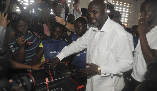 Former soccer star George Weah, Presidential candidate for the Coalition for Democratic Change cast his vote during a Presidential election in Monrovia, Liberia. Tuesday Oct. 10, 2017. Liberians gathered in masses under the bright sun Tuesday to vote in an election that for the first time in more than 70 years will see one democratically elected government hand power to another. (AP Photo/Abbas Dulleh)