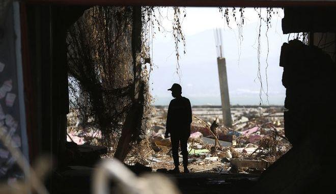 Άντρας στέκεται στα συντρίμμια της πόλης Παλού που ισοπεδώθηκε από την πολύ ισχυρή σεισμική δόνηση και τα παλιρροϊκά κύματα