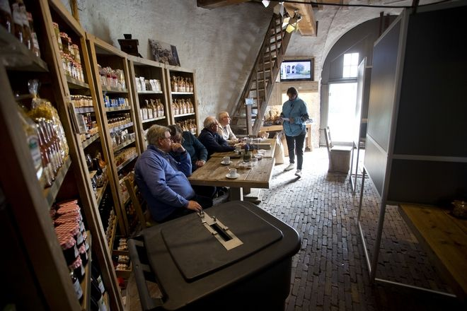 A voter enters the Kerkhovense Molen, a windmill turned polling station in Oisterwijk, south central Netherlands, Wednesday, March 15, 2017. Amid unprecedented international attention, the Dutch go to the polls Wednesday in a parliamentary election that is seen as a bellwether for the future of populism in a year of crucial votes in Europe. (AP Photo/Peter Dejong)