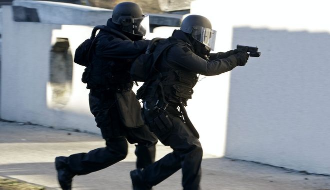 Members of Geneva's Intervention Group Police walk in front of a house during a police drill ahead of the Euro 2008 soccer championships, in Geneva, Switzerland, Tuesday, November 27, 2007. (KEYSTONE/Salvatore Di Nolfi)