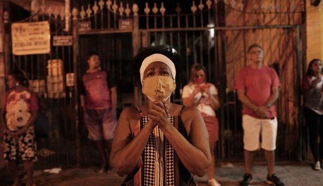 Μια γυναίκα στη Βραζιλία προσεύχεται, φορώντας μάσκα Izquierdo)