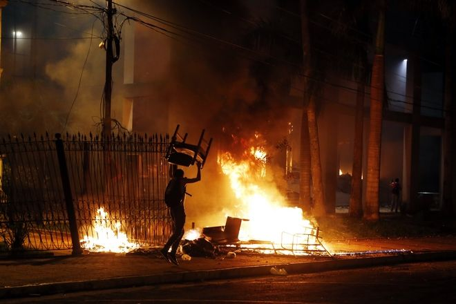 A protester carries a chair to a fire outside the congress building during clashes between police and protesters opposing an approved proposed constitutional amendment that would allow the election of a president to a second term, in Asuncion, Paraguay, Friday, March 31, 2017. Some protesters broke through police lines and entered the first floor, where they set fire to papers and furniture. Police used water cannon and fired rubber bullets to drive demonstrators away from the building while firefighters extinguished blazes inside. (AP Photo/Jorge Saenz)