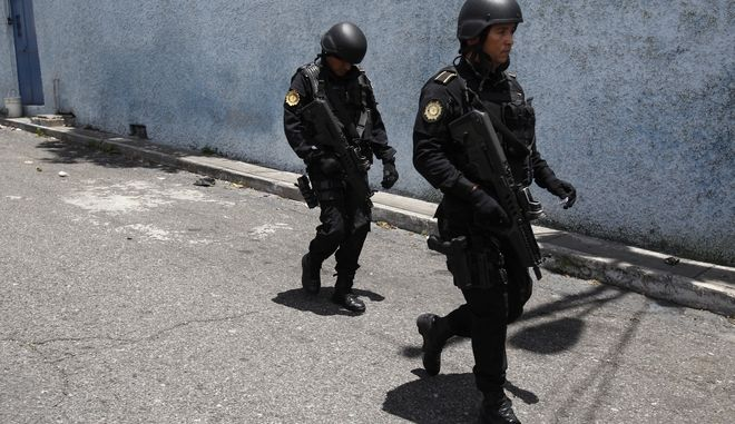 Special forces of the National Civil Police search for inmates who escaped from the Juvenile Correctional Center Gaviotas in Guatemala City, Monday, July 24, 2017. A new riot at a juvenile prison in the center of the capital of Guatemala left at least 12 injured, according to firefighters. (AP Photo/Moises Castillo)