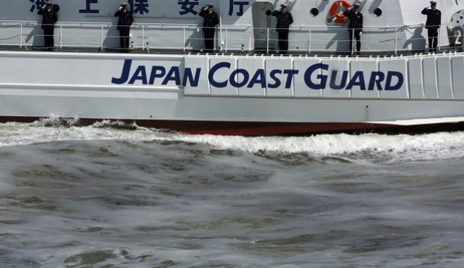 Members of Japan Coast Guard salute from a ship during an exercise in Tokyo Bay Saturday, May 20, 2017, in Tokyo. Japan Coast Guard conducted an annual review of their fleet and drills. (AP Photo/Eugene Hoshiko)