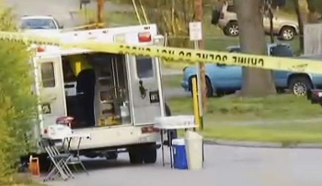 In this image made from video provided by WRCB-TV, an ambulance parks near the scene of a fatal officer-involved shooting in Chattanooga, Tenn., Wednesday, March 29, 2017. Police in Tennessee called to a report of an armed person early Wednesday fatally shot a suspect who was a sheriff's department employee, officials said. (WRCB-TV via AP)