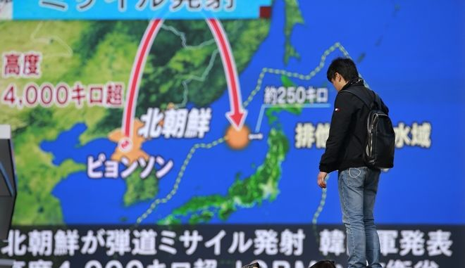"""FILE - In this Nov. 29, 2017, file photo, a man stands in front of a huge screen showing TV news program reporting North Korea's missile launch, in Tokyo. Japanese Prime Minister Shinzo Abe's Cabinet approved Japan's biggest 5.19 trillion yen ($46 billion) defense budget on Friday, Dec. 22, 2017, to bolster ballistic missile defense capability amid escalating threats from North Korea. The Japanese letters on top reads: """"Missile launch."""" (AP Photo/Shizuo Kambayashi)"""