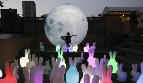 In this Oct. 2, 2018, photo, a child dances as she is silhouetted by a balloon moon installation at a art district in Beijing, China. The installation art is part of a parent and child event coinciding with the Chinese National Day. (AP Photo/Ng Han Guan, File)