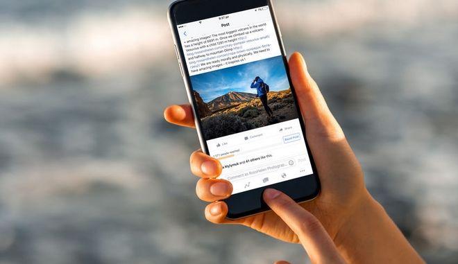 Μια γυναίκα παρακολουθεί το Facebook στο κινητό της.