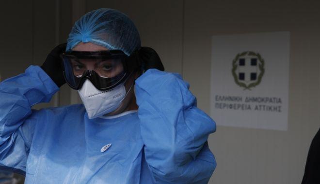 Εργαζόμενη στον τομέα της υγείας, φορά στολή και μάσκα προστασίας από Covid - 19