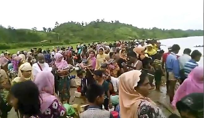 In this Oct. 5, 2017, video released by Arakan Rohingya National Organization, villagers are seen preparing to cross a river towards  the Maungdaw township in the Rakhine state that borders Bangladesh. More Rohingya Muslims fleeing violence in Myanmar are streaming toward the border, despite government assurances that it is stopping the exodus of refugees to Bangladesh. (Arakan Rohingya National Organization via the AP)