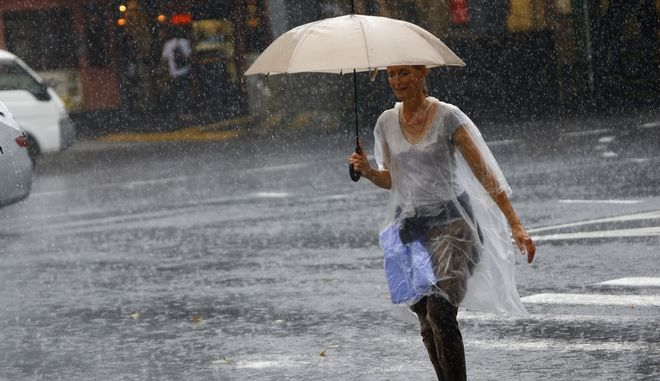A woman holding an umbrella crosses a street in heavy rain in Tokyo's Ginza shopping district, Wednesday, Sept. 9, 2015. Heavy rain caused by a typhoon passing through central Japan hit the Tokyo metropolitan area in the day. (AP Photo/Shizuo Kambayashi)