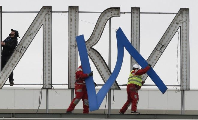Workers remove a giant letter from a sign reading in Macedonian