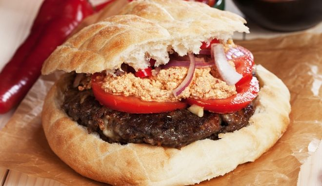 Pljeskavica, serbian style ground beef burger with tomato, onion and urnebes salad