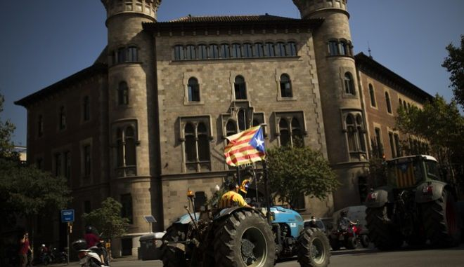 A man with the estelada, or Catalonia independence flag, steers a tractor during a protest by farmers in Barcelona, Friday, Sept. 29, 2017. Authorities in Catalonia aim to ensure that a disputed referendum on independence from Spain will take place peacefully on Sunday despite a crackdown on the vote by the national government, the region's interior chief said. (AP Photo/Francisco Seco)