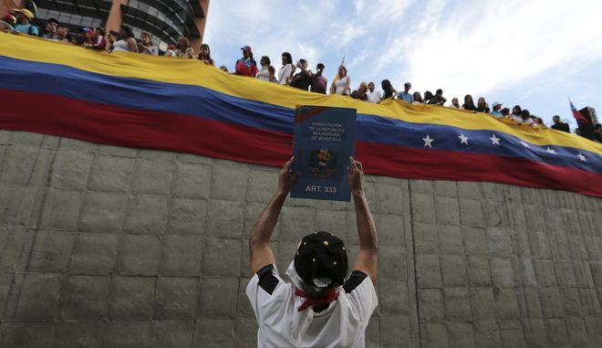 A demonstrator shows a copy of the National Constitution during a tribute to those killed during protests against Venezuela's President Nicolas Maduro, in Caracas, Venezuela, Monday, July 24, 2017.  The opposition is staging daily protests days before President Maduro launches the rewriting of the country's constitution. (AP Photo/Fernando Llano)