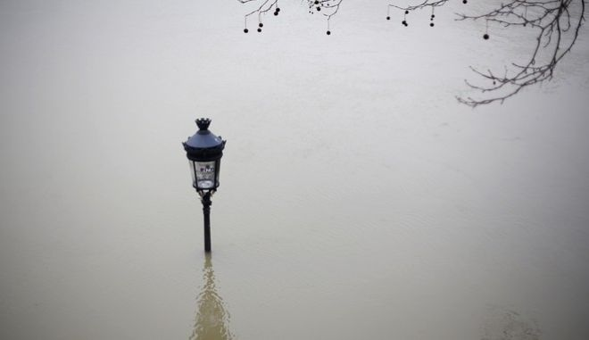 A flooded street lamp is pictured next to the river Seine in Paris, Saturday, Jan. 27, 2018. Floodwaters were nearing their peak in Paris on Saturday, with the rain-swollen Seine River engulfing scenic quays and threatening wine cellars and museum basements. (AP Photo/Thibault Camus)