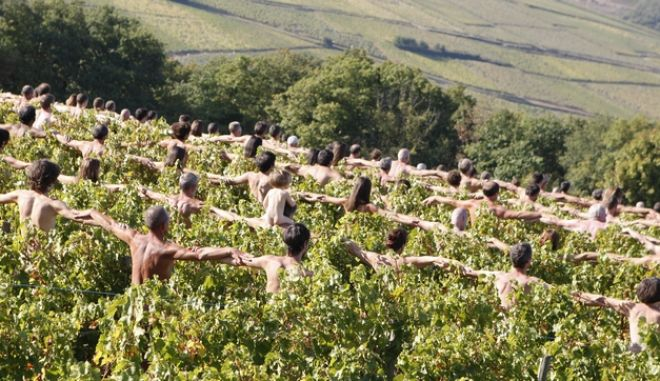 Some 500 nude models pose for U.S. artist and photographer Spencer Tunick standing on an elevated platform third from left, uses a megaphone to direct about 500 naked people in the vineyard of Fuisse, near Macon, Central France, Saturday Oct. 3, 2009. The environmental group Greenpeace commissions Tunick to take pictures of nude volunteers in the vineyard to call attention to the issue of global warming and its impact on wine production. (AP Photo/Francois Mori) ** NO SALES  EDITORIAL USE ONLY **