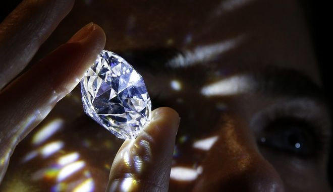 """A 102.34, carat, D colour and flawless white diamond held by a model is displayed at Sotheby's auction house in London, Thursday, Feb. 8, 2018. The diamond is the world largest known round brilliant diamond to have achieved """"perfection in all critical criteria - Colour, Clarity, Cut and Carat"""", and is expected to reach considerably over 33.7 million dollars by private sale in London. (AP Photo/Alastair Grant)"""