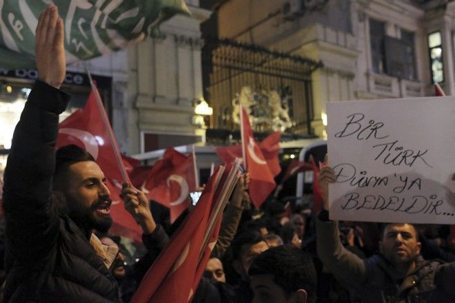 """Supporters of Turkey's President Recep Tayyip Erdogan gather outside the Dutch consulate during a protest, in Istanbul, early Sunday, March 12, 2017. Turkey and the Netherlands sharply escalated a dispute between the two NATO allies on Saturday as the Dutch withdrew landing permission for the Turkish foreign minister's aircraft, drawing Turkish President Recep Tayyip Erdogan to call them """"fascists"""". (AP Photo)"""