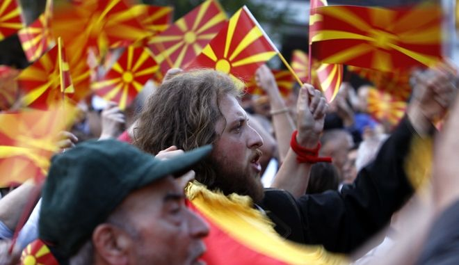 People wave Macedonian flags during a paceful protest in front of the EU mission building in Skopje, Macedonia, Friday, April 28, 2017.  About 2,000 protesters have gathered in Macedonias capital Skopje to demand new elections to try and break the countrys political deadlock, a day after violent protests inside the countrys parliament. (AP Photo/Boris Grdanoski)