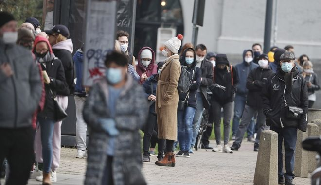 People queue in line to be tested for coronavirus at the Solec Hospital in Warsaw, Poland, Friday, Oct. 23, 2020. Polands government has announced the entire country will become a red zone of strict anti-COVID-19 restrictions starting Saturday, just short of a lockdown. (AP Photo/Czarek Sokolowski)