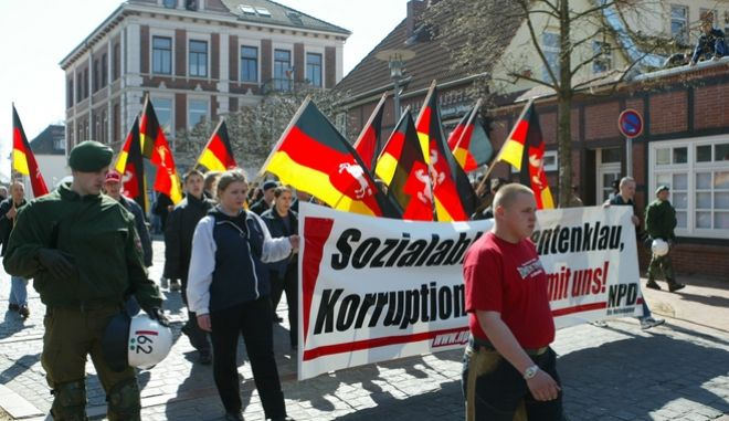 Some 200 neo Nazis holding banners and waving German flags with the Lower-Saxony coat of arms march through the city of Verden, northern Germany, Saturday, April 2, 2005. Police deployed several hundred policemen to ensure the neo Nazi march being seperated from a simultanious rally of some 750 anti-rightwing demonstrators. (AP Photo/Joerg Sarbach)