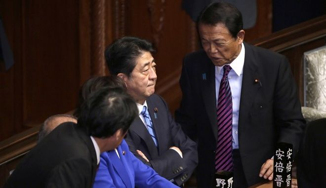 Japanese Prime Minister Shinzo Abe, center, talks with Finance Minister Taro Aso, right, at lower house of the parliament in Tokyo Thursday, Sept. 28, 2017. Abe dissolved the lower house and called a snap election for next month as expected. (AP Photo/Eugene Hoshiko)