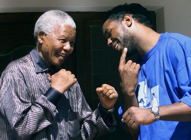 British heavyweight boxer Lennox Lewis (R) shows Former President Nelson Mandela April 23,2001, his jaw were he took a knockout punch from challenger American Hasim Rahman in the fifth round of Sunday's heavyweight championship fight at Carnival City in Brakpan. Rahman, who scored one of boxing's biggest upsets, flew home to the United States after the fight.  JN/ - RTR13ULV