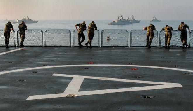 Στρατιώτες κοιτούν πολεμικά πλοία έξω από τη Λάρνακα
