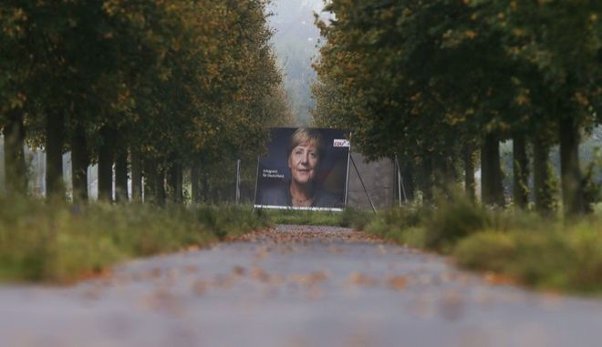 An election poster of German Chancellor Angela Merkel stands at the end of an alley in Frankfurt, Germany, Wednesday, Sept. 20, 2017. German elections will be held on upcoming Sunday. (AP Photo/Michael Probst)